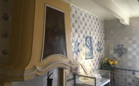 Foto tussenkamer met beschilderde schouw uit Workum en16e en 17e eeuwse tegeltableaus op de wanden